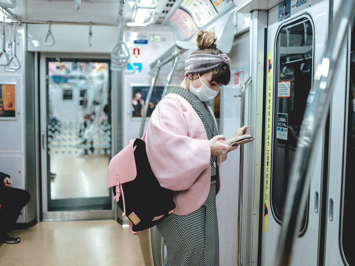 スターシャがマスクとバックパックCLÄSSY で電車に乗車中。立って携帯を見ている