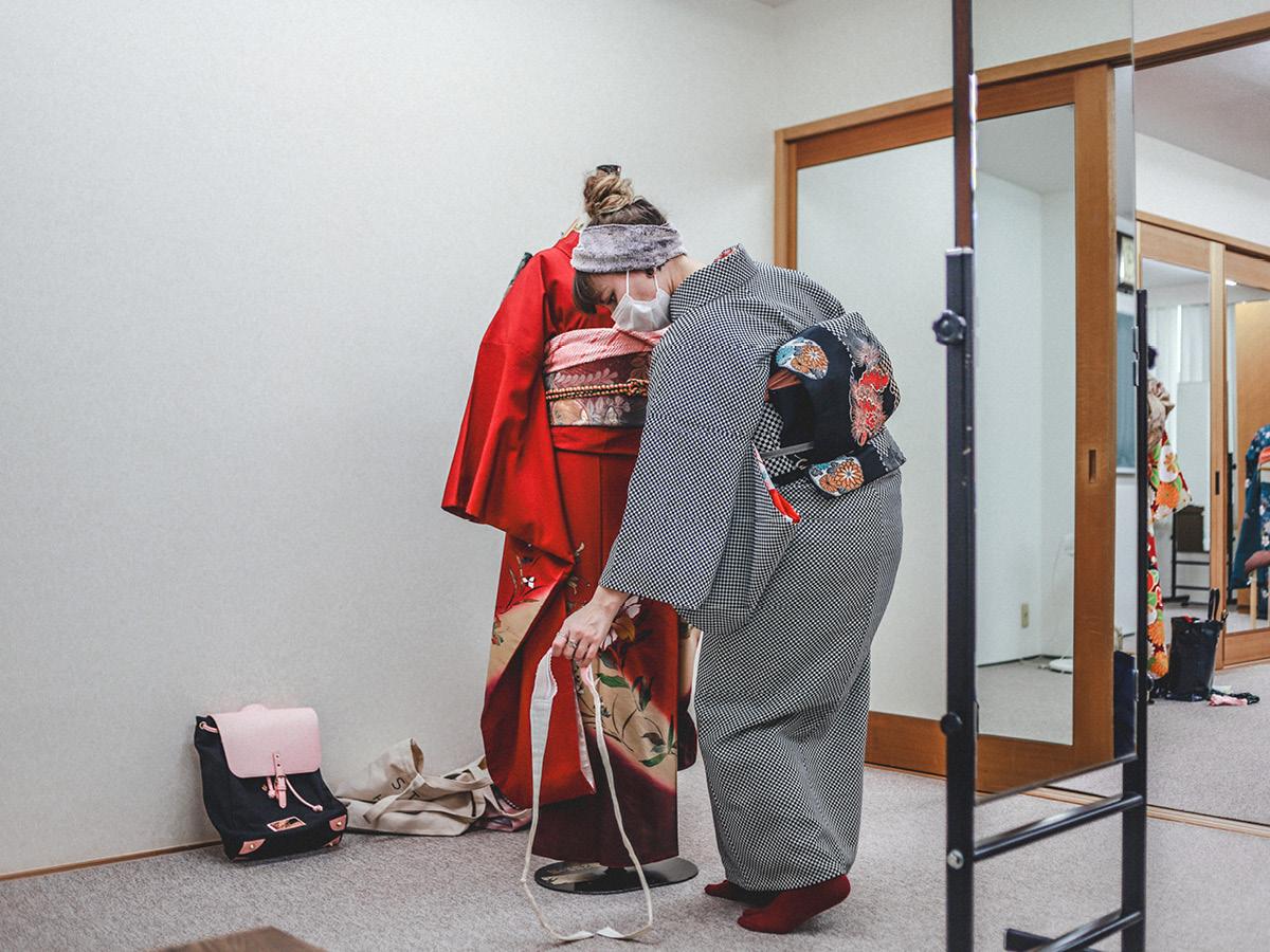 着物スタイリストスターシャが着物を着付ける練習をしている。バックパックCLÄSSY は壁の横に置いてある